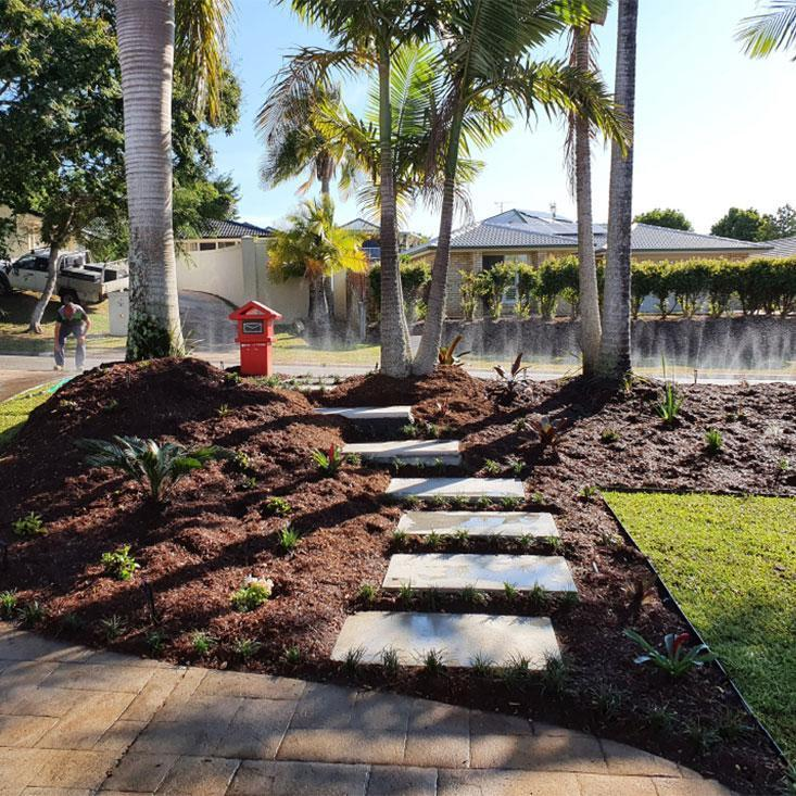 Image is circle shaped and contains a photo of landscaping underway with paver steps leading through garden
